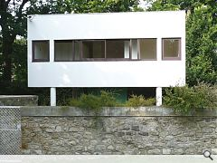 "A trademark white box sits on ""pilotis"" with a panoramic window"